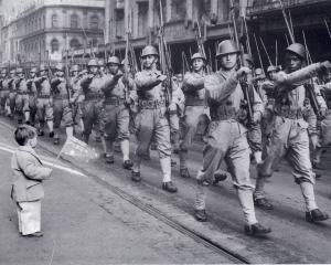Watched by a small boy waving an Australian flag, troops of the Netherlands East Indies Army march along Swanston Street, Melbourne on United Nations Day, 14 June 1943.