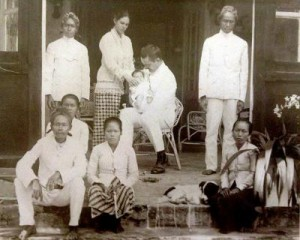Jan Kuneman holding baby Jan, with mother Drethe standing, and Indonesian workers on the steps of the family home, Java, 1930.